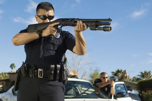 Police officer with shotgun by patrol car