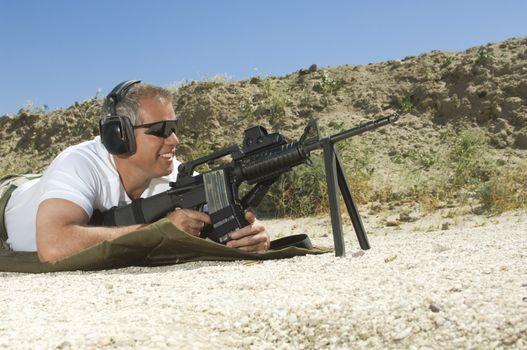 Man lying on ground aims machine gun at firing range during combat training