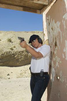 Police woman aiming handgun at firing range during combat training