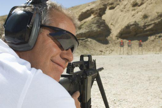Closeup of a man aiming machine gun at firing range during combat training