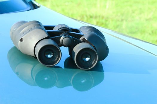 On the hood of a blue car is the binoculars.