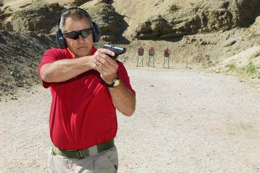 Man aiming handgun at shooting range during weapons training