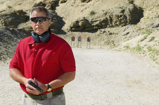 Portrait of a man holding hand gun at firing range
