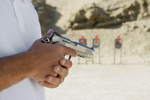 Midsection of a man holding handgun at firing range during training