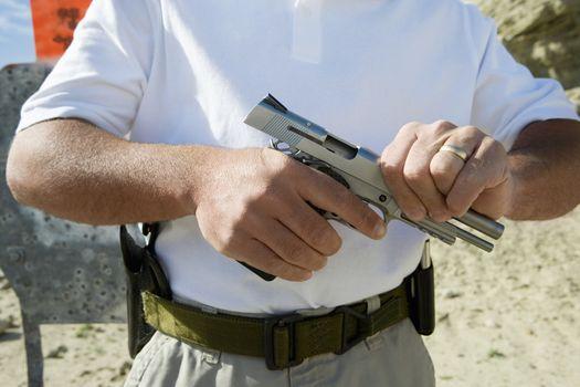 Midsection of a man loading hand gun at firing range