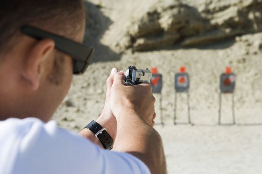 Closeup of man aiming hand gun at firing range