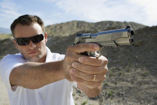 Man aiming hand gun at firing range in desert