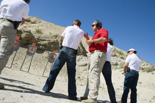 Instructor assisting people aiming guns at firing range