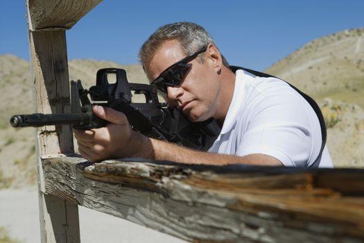 Man aiming machine gun at firing range in desert