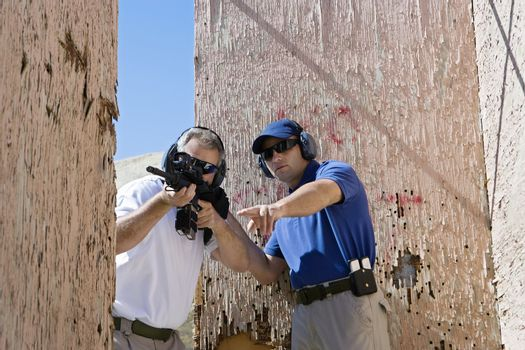 An Instructor assisting man with machine gun at firing range during combat training