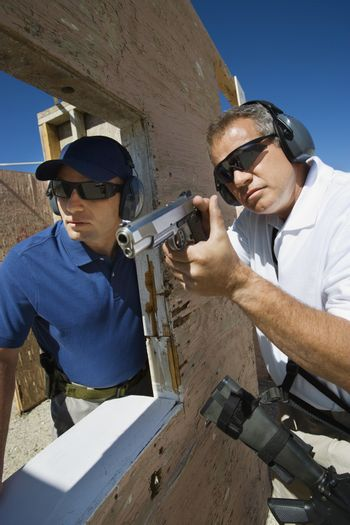Instructor assisting man with hand gun at firing range during combat training