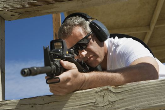 Caucasian man aiming machine gun at firing range