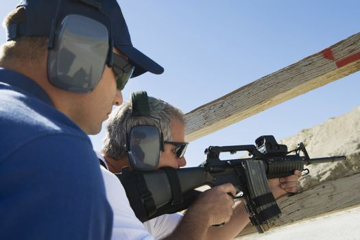 Instructor with man aiming machine gun at firing range during combat training