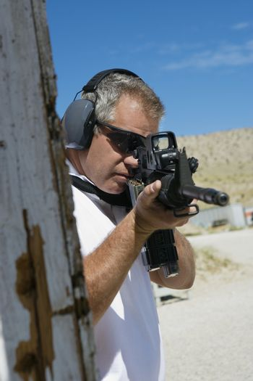 Caucasian male officer aiming machine gun at firing range during combat training