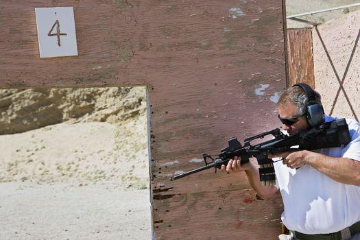 Man aiming machine gun at firing range during combat training