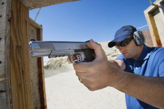 Man aiming hand gun at firing range during combat training