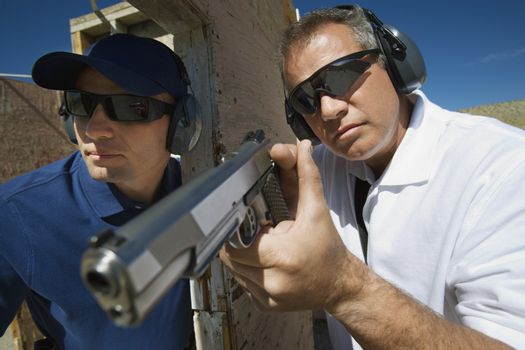 Instructor assisting officer with hand gun at firing range during combat training