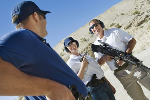 Instructor with man and woman with weapons at firing range in desert