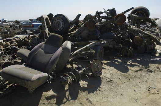 Crushed and damaged car parts at a junkyard