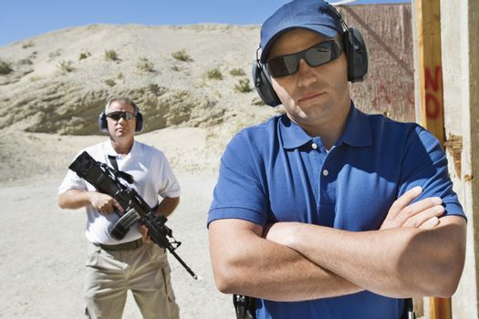 Portrait of two men with weapons at firing range in desert