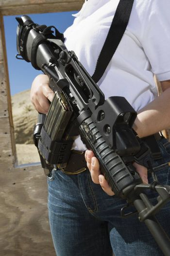 Midsection of a woman holding machine gun at firing range