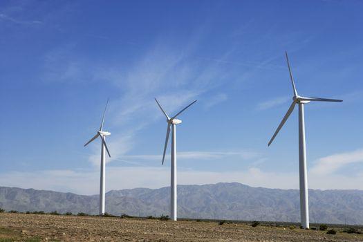 Three wind turbines in desert against blue sky