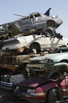 Stack of worn and brokendown cars at junkyard