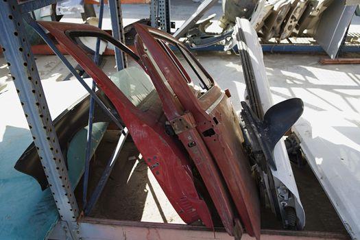 Damaged and worn out car parts at junkyard