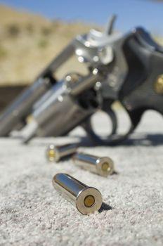 Closeup of a bullets beside gun