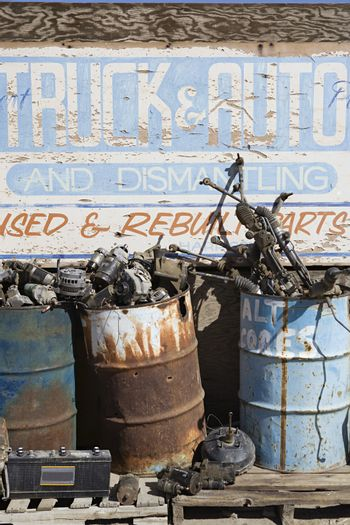 Sign and rusty barrels with obsolete car parts in junkyard