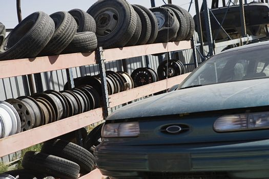 Tires and treads on rack with car at scarp yard