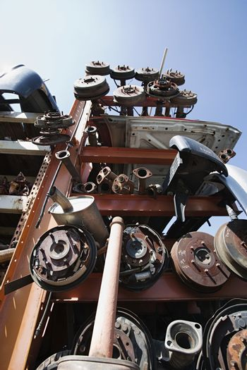 Low angle view of obsolete metal car parts at junkyard against clear sky
