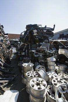Waste and broken down vehicle parts at junkyard