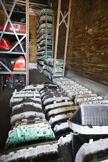 Interior of storeroom with old vehicle parts kept on floor and racks