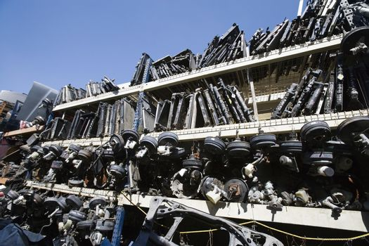 Old waste vehicle parts on rack at an automotive scrap yard