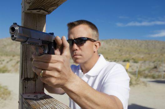 Man aiming handgun at firing range during weapons training