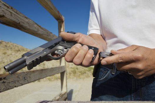 Closeup of a man loading magazine into gun at firing range
