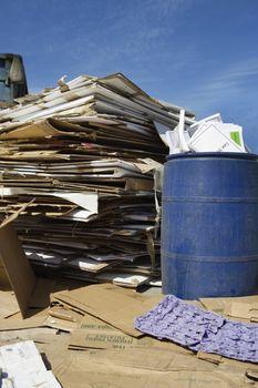 Stack of cardbox boxes with waste bin in junkyard