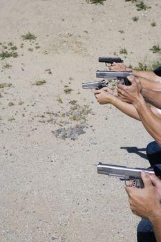 Peoples aiming guns at firing range close up of hands