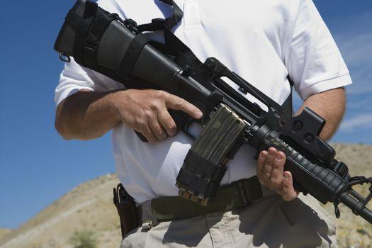 Midsection of a man holding machine gun at firing range