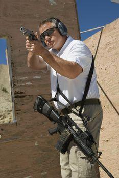 Man aiming handgun at firing range during combat training