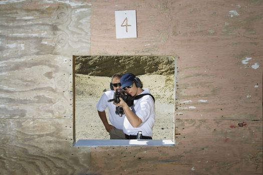 Male instructor with woman aiming machine gun at firing range during combat training