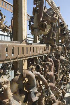 Old rusty auto parts on rack at junkyard
