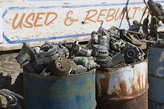 Torndown and brokenup car parts in barrels at junkyard