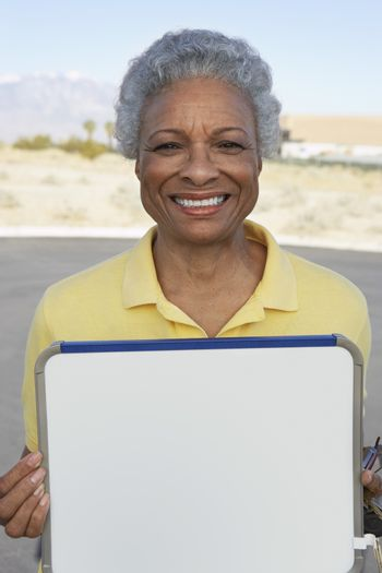 Portrait of a happy senior woman holding signboard