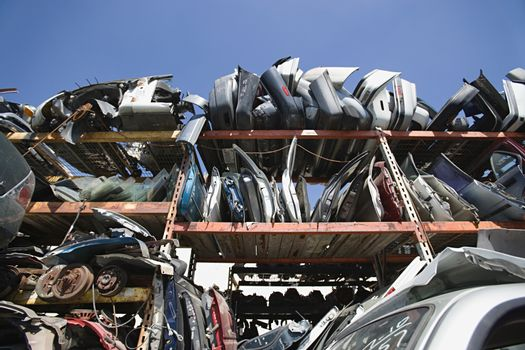 Low angle view of scrapped vehicle parts in junkyard