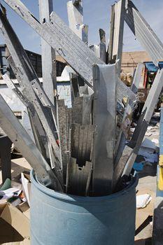 Metal parts in garbage bin at junkyard