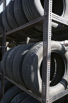 Old tires arranged in shelves in junkyard