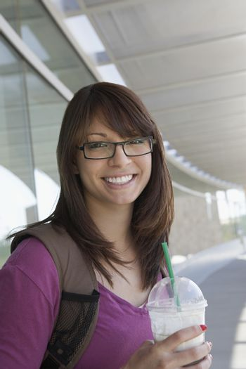 Portrait of a happy young female student holding disposable glass
