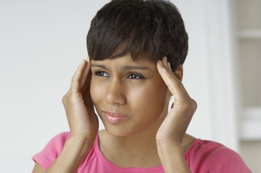 Closeup of a tensed African American woman with hands on temples
